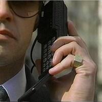 Homme en complet tenant un téléphone cellulaire à son oreille, avec une grosse bague en or à son auriculaire