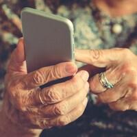 Les mains d'une femme âgée sur un téléphone cellulaire.