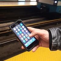 Un téléphone intelligent tenu par un utilisateur du métro