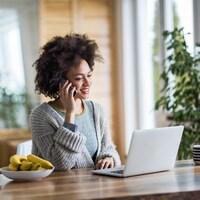 Une jeune femme au téléphone devant un ordinateur.