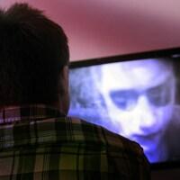 Un jeune homme regarde un film d'horreur à la télévision.