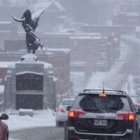 Le centre-ville de Sherbrooke sous la neige. Les voitures circulent ici sur la rue King Ouest en direction de la rue Wellington. On aperçoit également à gauche le cénotaphe.