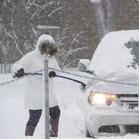 Une femme déneige sa voiture pendant une tempête de neige au Nouveau-Brunswick en janvier 2018.