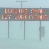 Une affiche routière prévient les automobilistes des conditions routières dangereuses.