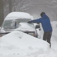Un homme déneige sa voiture à Montréal.