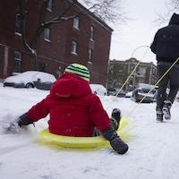 Un homme tire un enfant assis dans un traîneau.