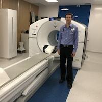 Un médecin pose à côté d'un scan, souriant.