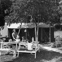 Famille installée avec tente et table à pique-nique sur un terrain de camping au Manitoba.