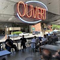 La terrasse d'un bar se reflète dans la vitrine de l'établissement