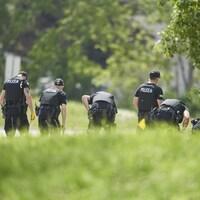 Une file de policiers recherche des preuves sur les lieux d'un accident de voiture à London, en Ontario, le lundi 7 juin 2021.