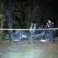 On voit la carcasse calcinée d'un véhicule qui a foncé dans un arbre. Un membre des forces de l'ordre observe les restes de ce véhicule derrière un cordon policier.