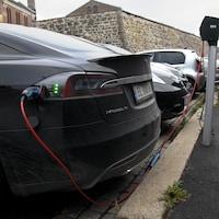 Une voiture électrique branchée à une borne de recharge dans un stationnement.