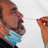 Un homme grimace lorsqu'on lui prélève de la narine un échantillon pour un test de dépistage de la COVID-19.