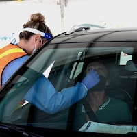 Une infirmière teste un homme par la fenêtre de sa voiture