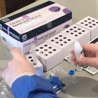 Un professionnel de la santé déballe une boîte de tests de dépistage rapides à la COVID-19.