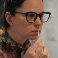 Une femme effectue un auto-dépistage du virus de la COVID-19.