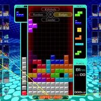Une capture d'écran du jeu vidéo Tetris 99 montrant une pile de petits blocs colorés empilés les uns sur les autres sur une grille.