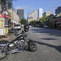 Une rue bordée de commerces et de bars et deux motos stationnées.