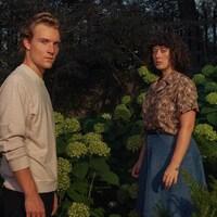 Un homme et une femme dans un jardin regardent la caméra.