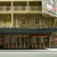 La façade d'un bâtiment de plusieurs étages avec une rangée de portes au rez-de-chaussée et une enseigne annonçant une cérémonie de remise des prix Tony.