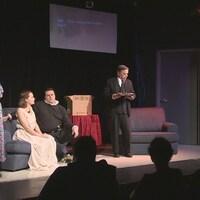 Les acteurs de la troupe Oksana de Regina sont sur scène. Le public les écoute attentivement.