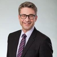 Theodor Bock, un homme portant des lunettes et un habit, sourit à la caméra.