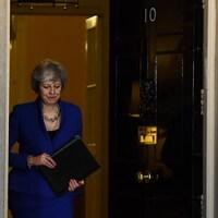 Theresa May, regardant au sol et tenant un porte-document, sort par l'entrée principale du 10 Downing Street, à Londres.