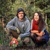 Thierry Bisaillon-Roy et Alice Berthe agenouillés devant une forêt, bouquet de fleurs à la main.