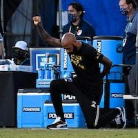 Thierry Henry, à genou sur un terrain de soccer, brandit le poing. Il porte l'inscription Black Lives Matter sur ses vêtements.