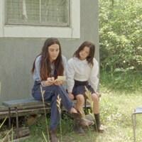 Une femme et une fillette sont assises et lisent une note.