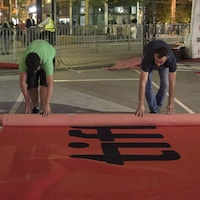 Des hommes déroulent un tapis rouge.
