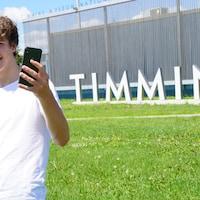 Un jeune homme se prend en selfie devant le signe de Timmins.