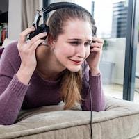 Une femme pleure en enlevant ses écouteurs.