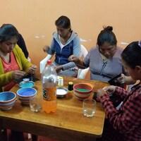Des tisserandes quechuas sont assises autour d'une table et fabriquent des ceintures fléchées.