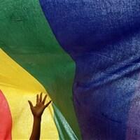 Une main s'agite devant un drapeau arc-en-ciel.