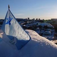 Un petit drapeau bleu et blanc arborant les symboles d'un ours polaire et d'un logo représentant une moitié de fleur de lys et une moitié de flocon est planté sur une butte de neige. En arrière-plan, la ville de Yellowknife.