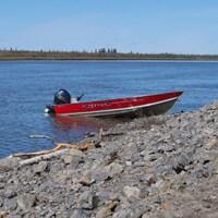 Un bateau accosté sur la grève d'un plan d'eau.