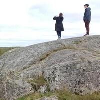 Deux personnes sur un rocher prennent une photo du paysage.