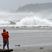 Un couple observe de grosses vagues qui se brisent sur la plage Chesterman à Tofino en Colombie-Britannique.