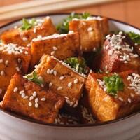 Des carrés de tofu cuit avec des graines de sésame.