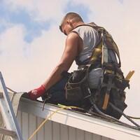 Un travailleur sur un toit sous un soleil brûlant.
