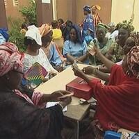 Des femmes qui échangent de l'argent autour d'une table.