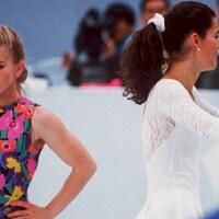 Tonya Harding, le visage triste, et Nancy Kerrigan, lui faisant dos, souriante sur la patinoire des Jeux olympiques de Lillehammer.