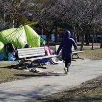 Un passant à hauteur d'un campement de fortune dans le parc Trinity Bellwoods.