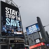 La Ville de Toronto presse les gens de rester à la maison sur les panneaux d'affichage du square Dundas.
