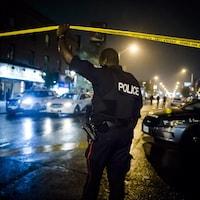 Un policier en uniforme soulève un ruban, qui sert à fermer un secteur lorsque les policiers établissent un périmètre de sécurité. La photographie a été prise le soir, car il fait sombre et seuls les néons et lampadaires illuminent la scène.