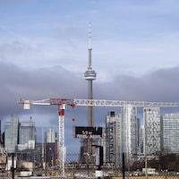 Une grue est visible devant la Tour CN entourée de tours à condominiums au centre-ville de Toronto.