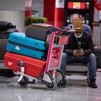 Un homme assis dans un aéroport avec des valises.