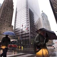 Deux passants traversent une grande artère en s'abritant sous des parapluies dans le quartier financier de Toronto.
