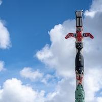 Un totem sur fond de ciel parsemé de nuages.